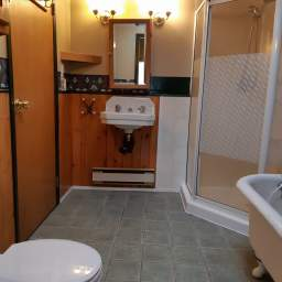Bathroom with clawfoot tub and corner shower + skylight and vaulted ceiling